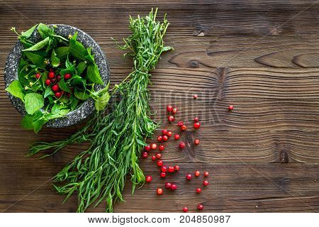 mortar with berries, herbs and spices ingredients on wooden desk background top view mock-up