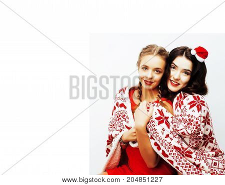 young pretty happy smiling blond and brunette woman girlfriends on christmas in santas red hat and holiday decorated plaid, lifestyle people concept close up