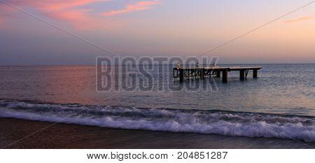 bulutlu bir gün batımında sahile vuran dalgalar