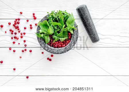 mortar with berries, herbs and spices ingredients on white wooden desk background top view mock-up