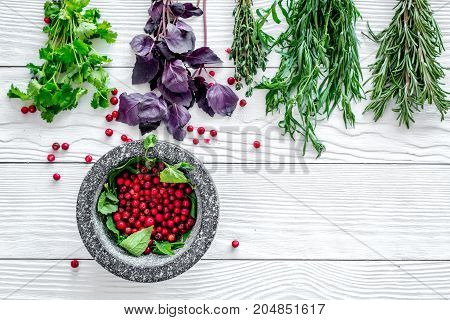 Food set with various herbs and berries for making spices and mortar on white wooden background top view mockup