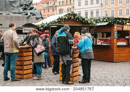 Prague, December 13, 2016: Old Town Square in Prague on Christmas Day. Christmas market in the main square of the city. Local residents and tourists eat national food called Tridlo. Holidays. Europe.
