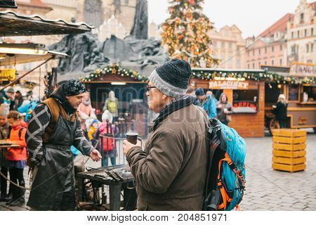 Prague, December 13, 2016: Old Town Square in Prague on Christmas Day. Christmas market in the main square of the city. An elderly tourist drinks hot wine mulled wine and looks at Christmas fun. Vacation. Europe.