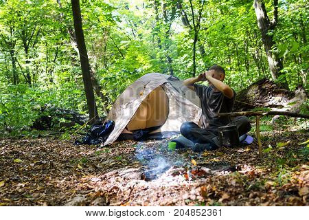 A Bonfire And A Tourist Tent In The Forest, The Tourist Is Resting Near The Tent.