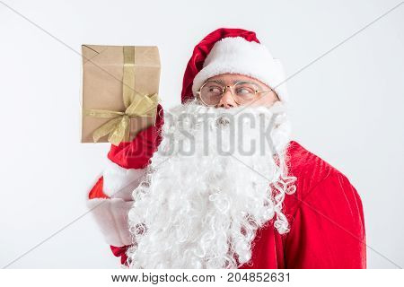 Portrait of cheerful Santa Claus holding gift box and looking at it with curiosity. He is standing isolated on background