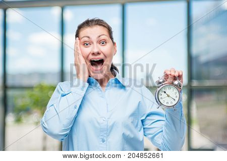 Emotional Businesswoman With An Alarm Clock In Shock In Office