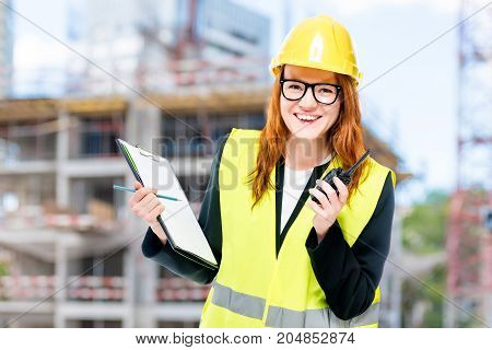 Woman Builder In Protective Clothes At Construction Site Walkie-talkie