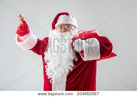 Portrait of happy Father Frost greeting everybody with New Year. He is holding jingle bell and looking at camera with excitement. Isolated