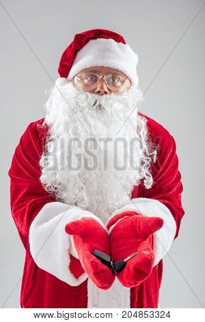 Waist up portrait of generous Father Frost showing key of personal transport in hands. He is standing and looking at camera with happiness. Isolated