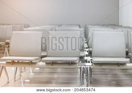 row of bench in the terminal of airport. empty airport terminal waiting area with chairs.