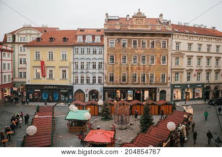 Prague, December 13, 2016: Old Town Square in Prague on Christmas Day. Christmas market in the main square. Celebrating Christmas. Happy local residents and tourists walk and rest. Europe. Holidays.