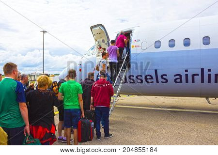 Brussels, Belgium - June 19, 2016: The people boarding the Brussels Airline aircraft. Passenger walking to the rear entrance of airplane at Brussels, Belgium on June 19, 2016