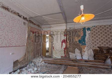 View the vintage room with fretwork on the ceiling of the apartment during under renovation remodeling and construction. Garbage of constraction materials and lamp in dark room during of disassembling floors and walls.