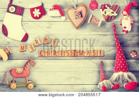 Christmas Greeting Card with Xmas Elements wooden cubes and Toys on Gray Wooden Background. Retro Style. Vintage Toned.
