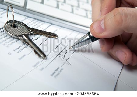 apartment keys mortgage loan document and human hand and a keyboard