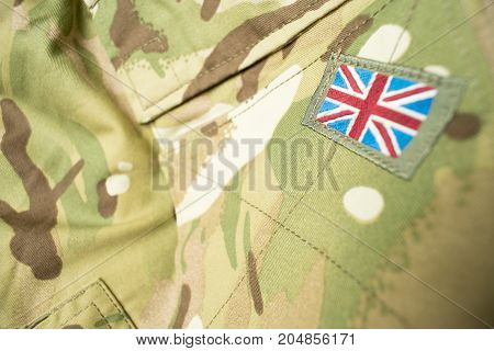 Union Jack / union flag badge on a British army camouflage uniform. Text / writing space around badge.