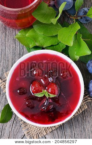 Plum jam in white bowl on wooden table rustic style top view