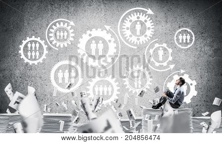 Businessman looking away while sitting on pile of documents among flying papers with social gear structure on background. Mixed media.