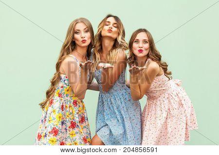 Sending Air Kiss. Three Best Friends Posing In Studio, Wearing Summer Style Dress Against Green Back
