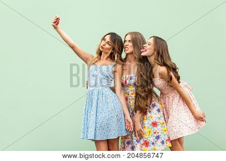 Beautiful Three Young Adult Fasion Model, Macking Selfie, Grimacing And Tongue Out. Green Background
