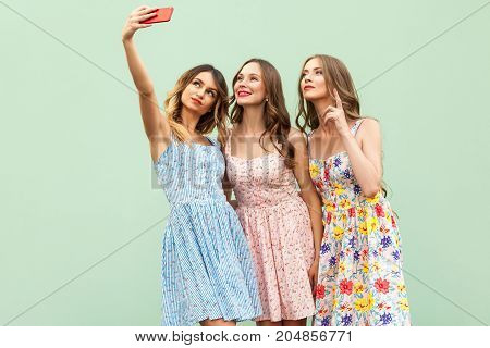 Young Adult Model, Macking Selfie, Looking In Smart Phone Screen And Smiling. Isolated On Green Back