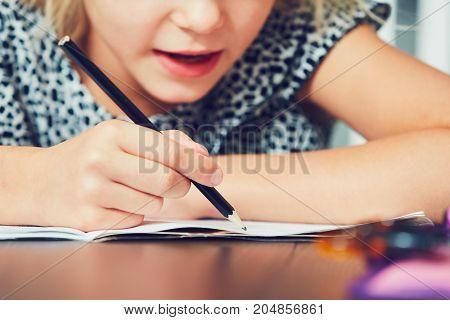 Little girl writing his homework for elementary school.