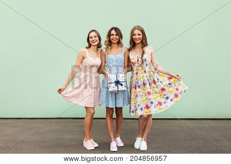 Charming Three Beautiful Young Adult Friends With Dresses And Present Box Smiling And Looking At Cam