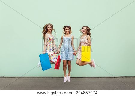 Happiness Beautiful Three Friends Jumping From Happy With Colorful Packets After Shopping.