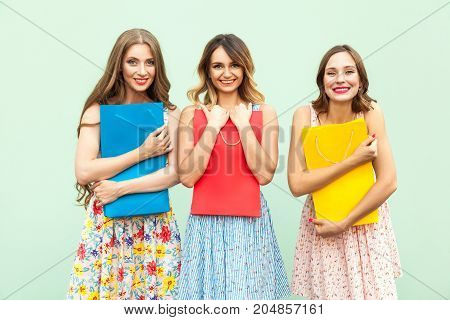 Beautiful Three Girl In Dress, Hug Her Colorful Bags.