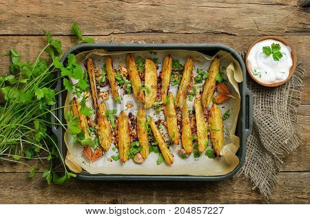 Baked potato wedges on wooden table top view. Vegetarian food