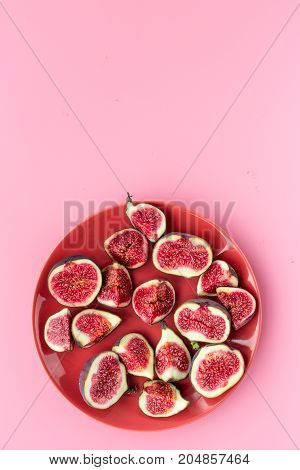 Fresh blue figs sliceson plate on pink background top view.