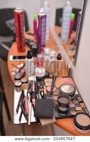 makeup products are lying on the table while the stylist is working. backstage. soft focus