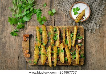 Vegetarian food. Potato wedges on wooden surfaces top view
