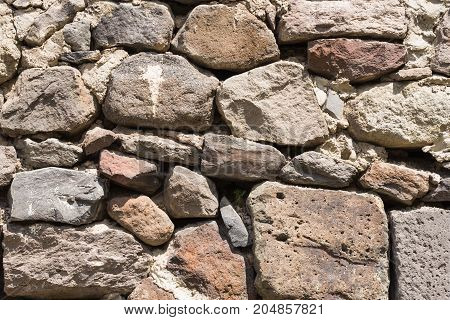 Old grey and brown rough stone wall closeup texture background selective focus shallow DOF.