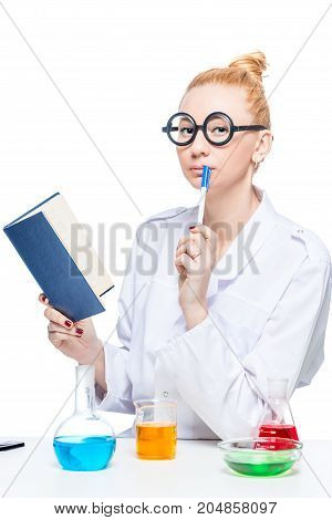 Thoughtful Funny Chemistry Student With A Book And Test-tubes At The Table