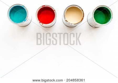 Paints in tin banks on white background top view.