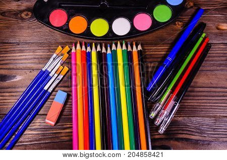 Set Of Different Drawing Tools. Watercolor Paints, Paintbrushes, Pens, Eraser On Wooden Table