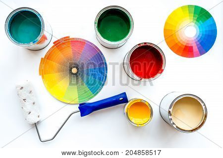 Choosing color for painting. Palette near roller and paints on white background top view.