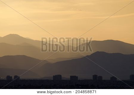 Rocky Mountain Sunset in Soft Pastel Colors with City Skyline Silhouette in Foreground