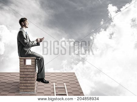 Young businessman sitting on house chimney with mobile phone in hands