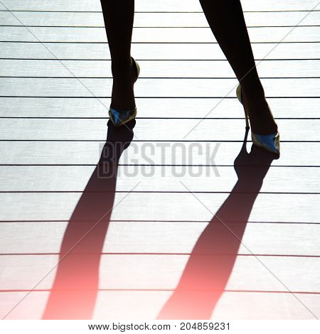 Female legs in golden shoes with high heels and dark shadow on wooden floor background. Fashion and accessories concept