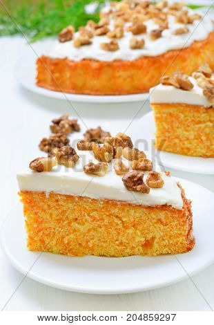 Appetizing piece of carrot cake with icing decorated walnut on white plate