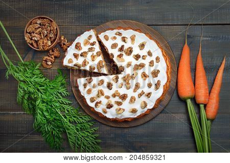 Homemade carrot cake fresh carrots and walnuts on wooden table top view