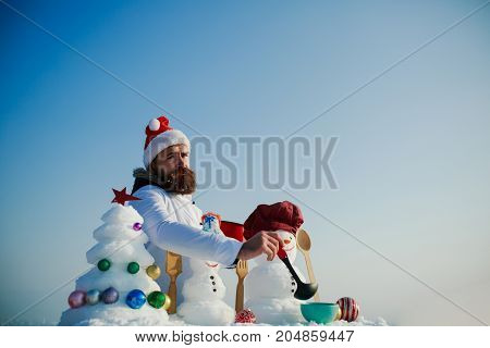 Man In Red Santa Hat Cooking On Winter Day