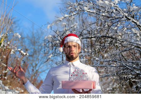 Merry Christmas and happy new year. Man holding present box in snow wood. Season greetings and xmas gifts. Macho in red santa hat on winter day. Holidays celebration concept.