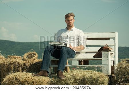 Secretary or assistant typing on typewriter on blue sky. Man sitting on bench on natural landscape. Macho working on sunny day. Vintage equipment and archaism. Summer vacation concept.