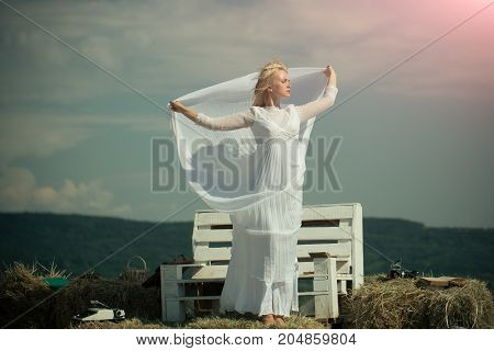 Girl in white dress on sunny day. Woman spreading arms on blue sky. Freedom and inspiration. Model enjoying nature on hay grass. Summer vacation concept.