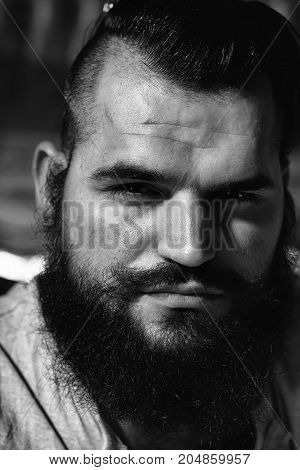 Closeup view portrait of one handsome serious young adult man with long black lush beautiful beard and moustache looking forward indoor on blurred background vertical picture
