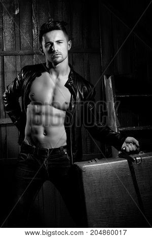 Handsome sexy sensual muscular stylish young man in leather jacket with bare torso standing with retro suit case near stairs indoor on wooden background vertical picture