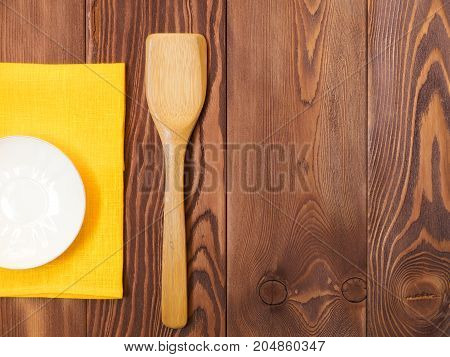 Plate on yellow tablecloth over wooden background. View from above